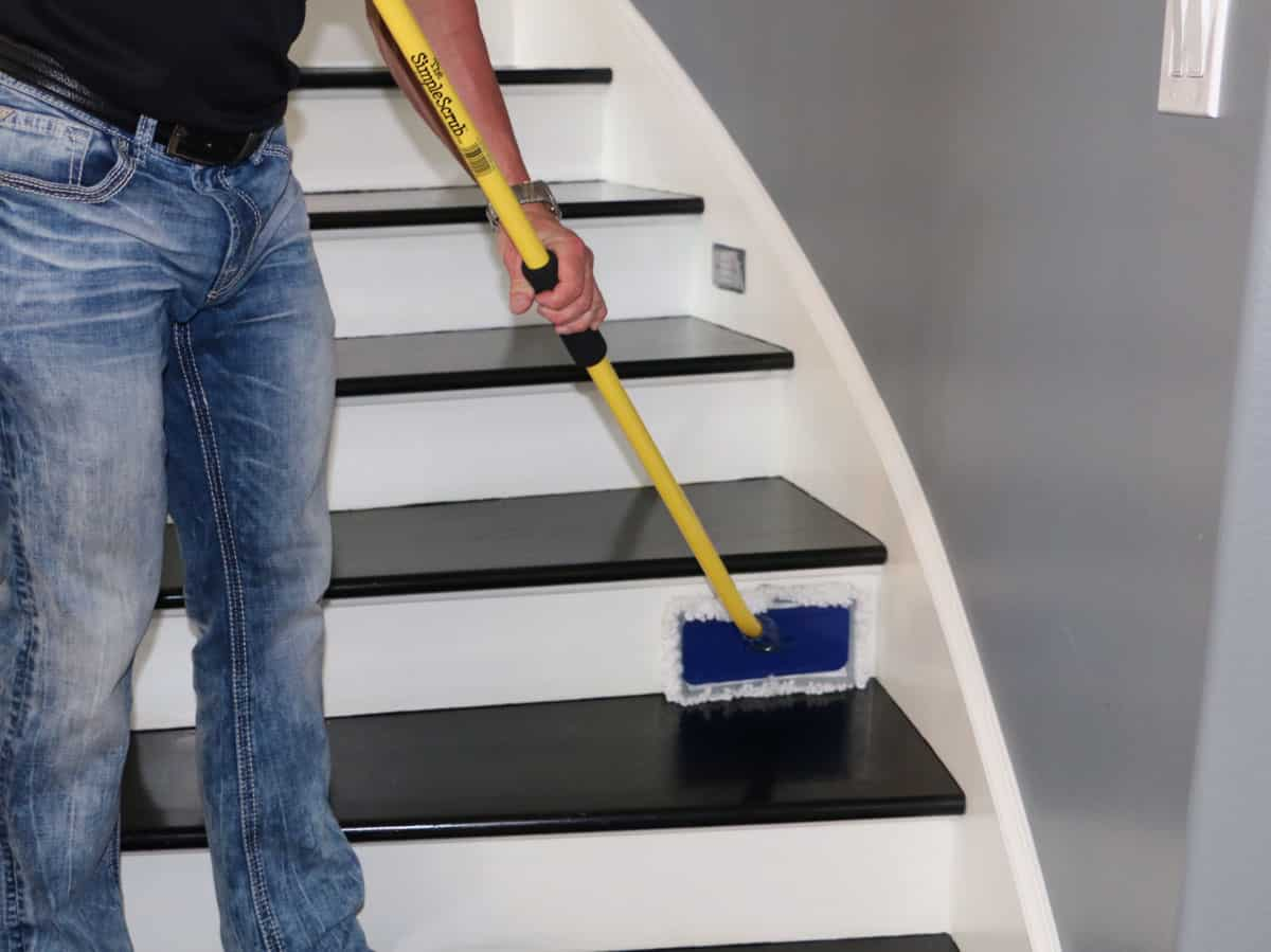 Man cleaning stairs with The Simple Scrub Original.